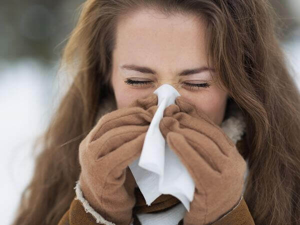 Young woman blowing nose in winter outdoors